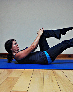 Pilates instructor doing a single leg extension