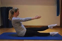 Pregnant woman doing seated leg lift abdominal exercise - lowering leg