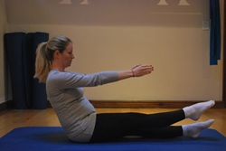 Pregnant woman performing abdominal exercise - single leg lift