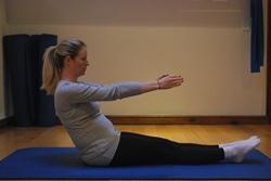 Pregnant woman doing seated leg lift abdominal exercise - leaning back