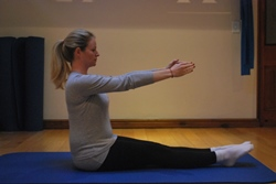 Pregnant woman doing seated leg lift abdominal exercise - starting position